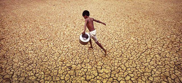Чернокожий ребенок в пустыне с ведром для воды