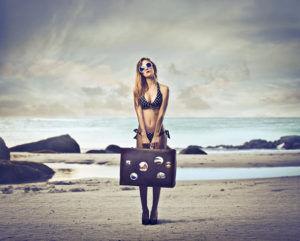 Девушка с чемоданом на берегу моря