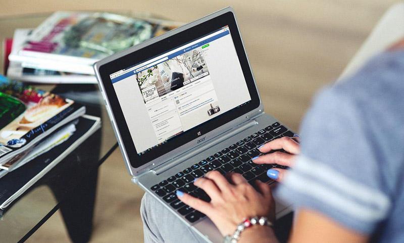 Женщина работает в Фейсбук на ноутбуке